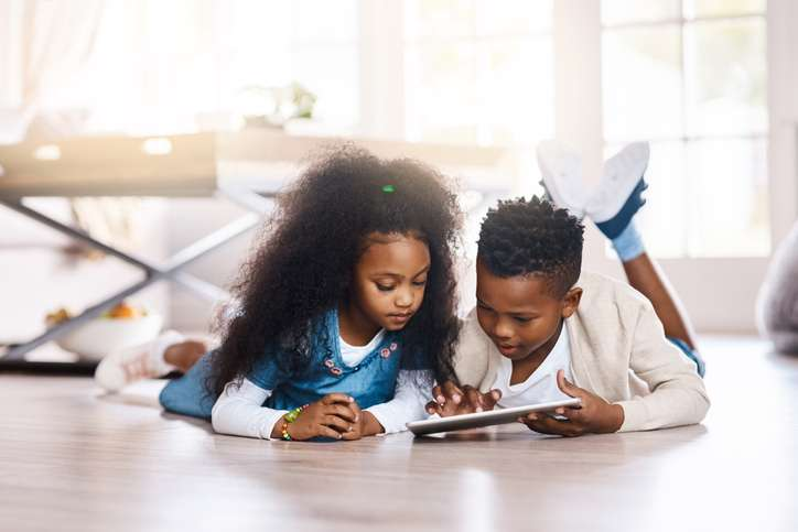Two children play a game on a tablet wile laying down on their living room floor.