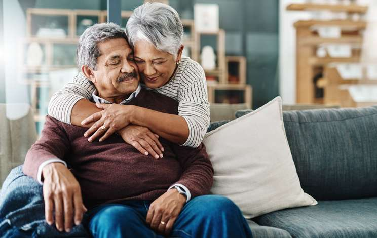 An older couple embraces on a sofa in their house