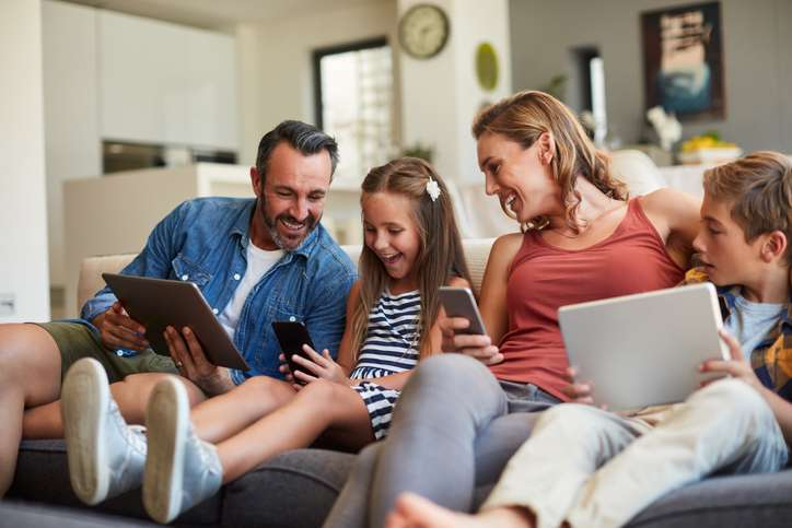 Family at home on a couch looking at mobile devices