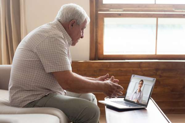 An elderly man sits in his living room talking to his doctor on a video call from his laptop.