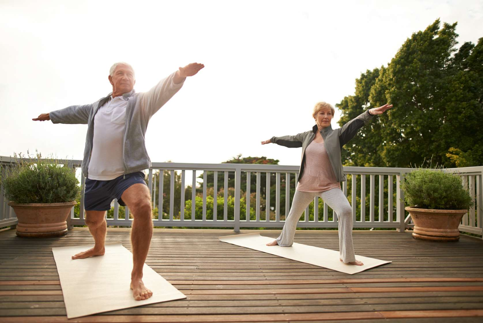 A senior married couple practicing yoga at home