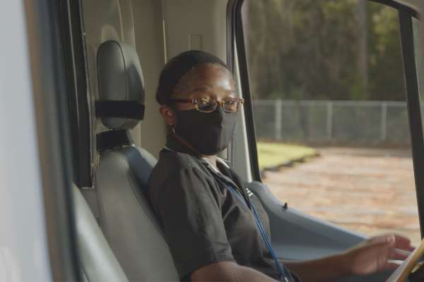 Shakeyla Grimes, a Black woman, sits in in the driver's seat of a campus shuttle. She is wearing a grey polo and a black protective face mask.