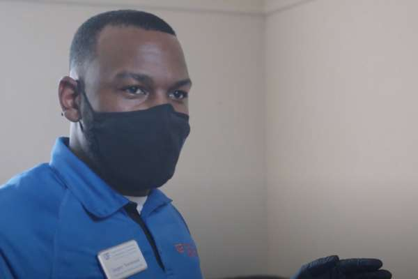 Jasper Norwood is a Black man with short cut hair. He stands in a room, and is wearing a blue University of Florida polo, a black protective face mask, and black gloves.
