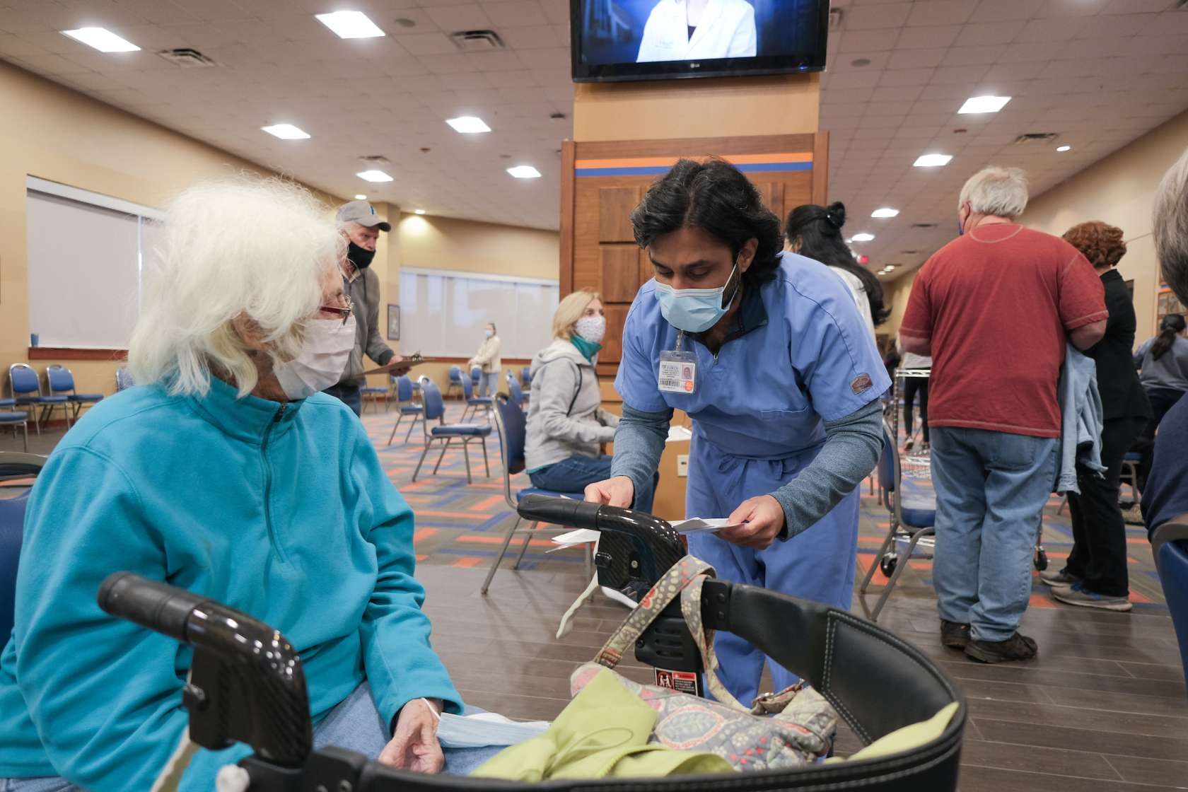A male health care worker wearing a mask discusses the vaccination with an older woman sitting next to her walker.