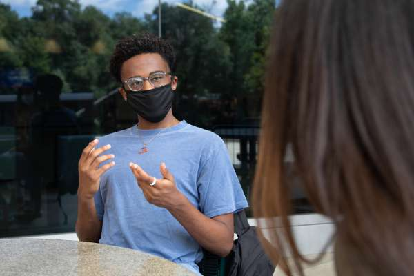 A young Black man talks to a woman at an outdoor table. He is wearing a cloth mask.