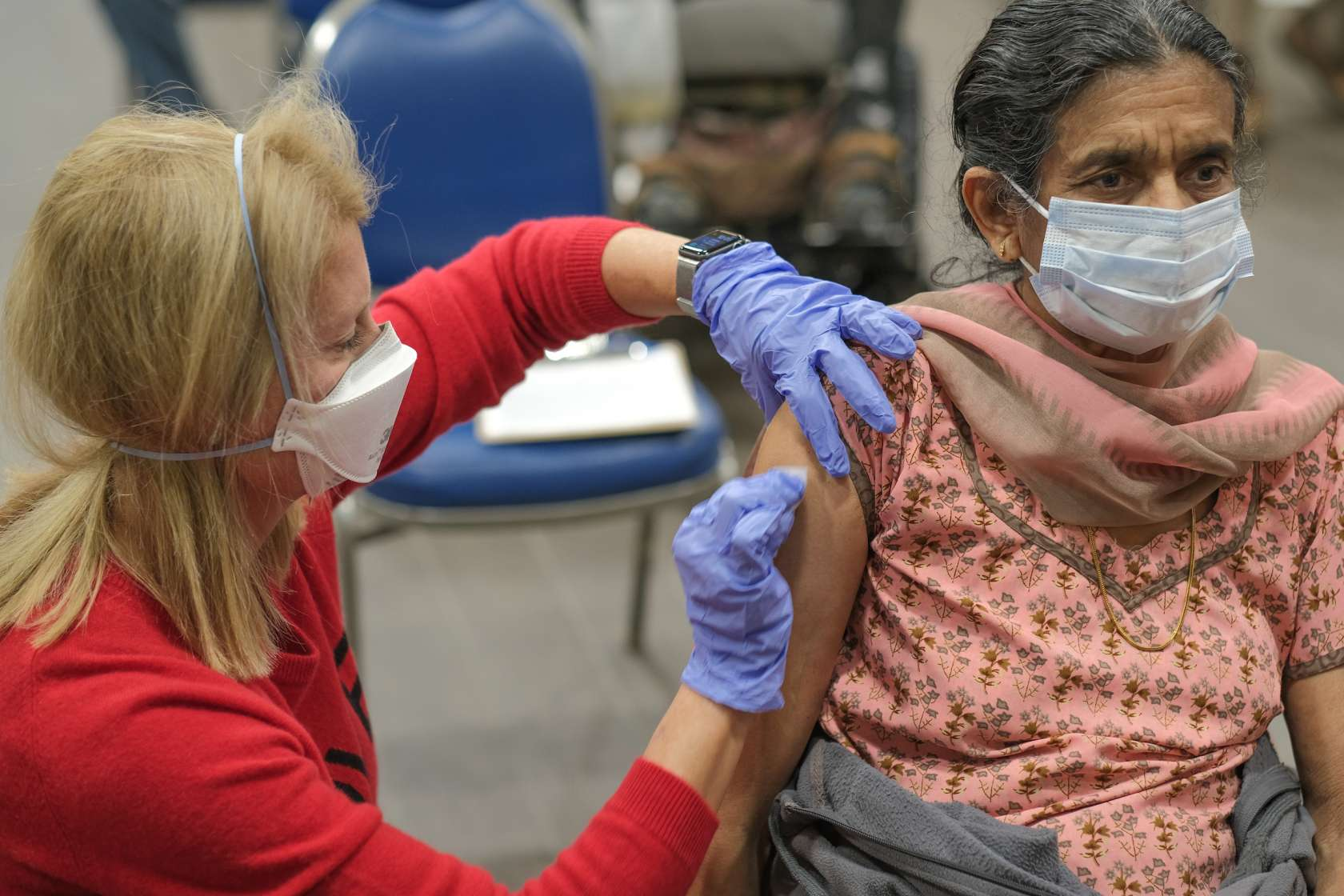 A light-skinned UF Health careworker, wearing red scrubs, gives a vaccination to an older woman with medium complexion.